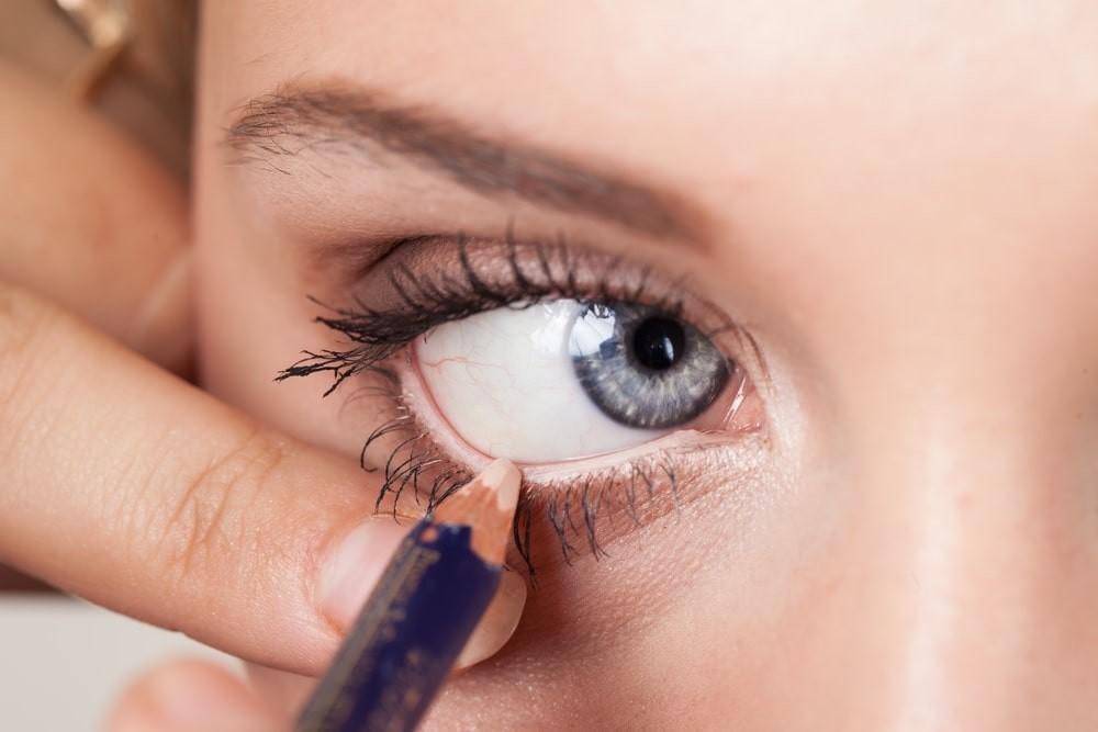 woman applying nude eyeliner to her lower waterline.