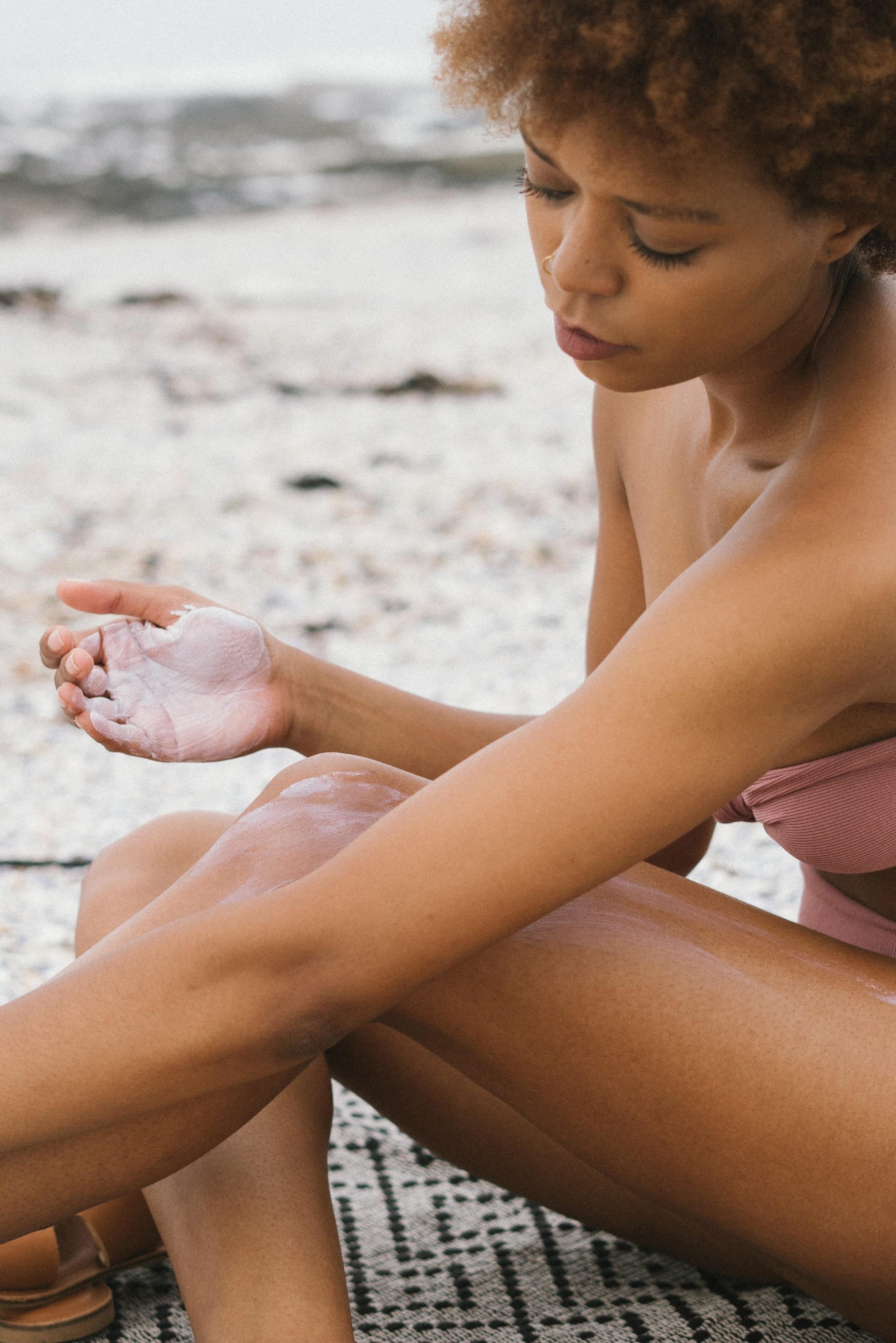 woman, wearing a pink bikini, applying sun protection during a heatwave
