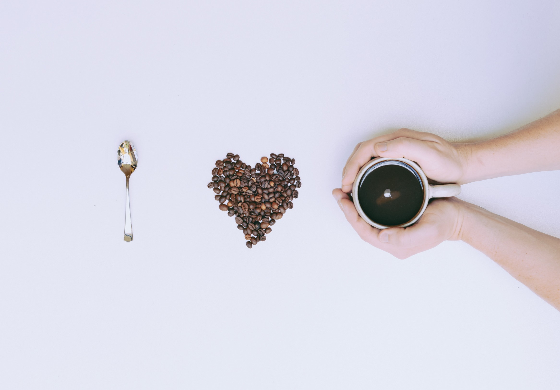 a single teaspoon, a heartshape filled with coffee beans and two hands holding a mug of black coffee - translating I heart coffee.