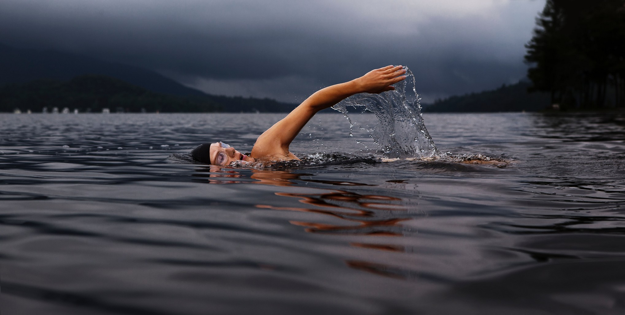 person swimming outside, within a loch.