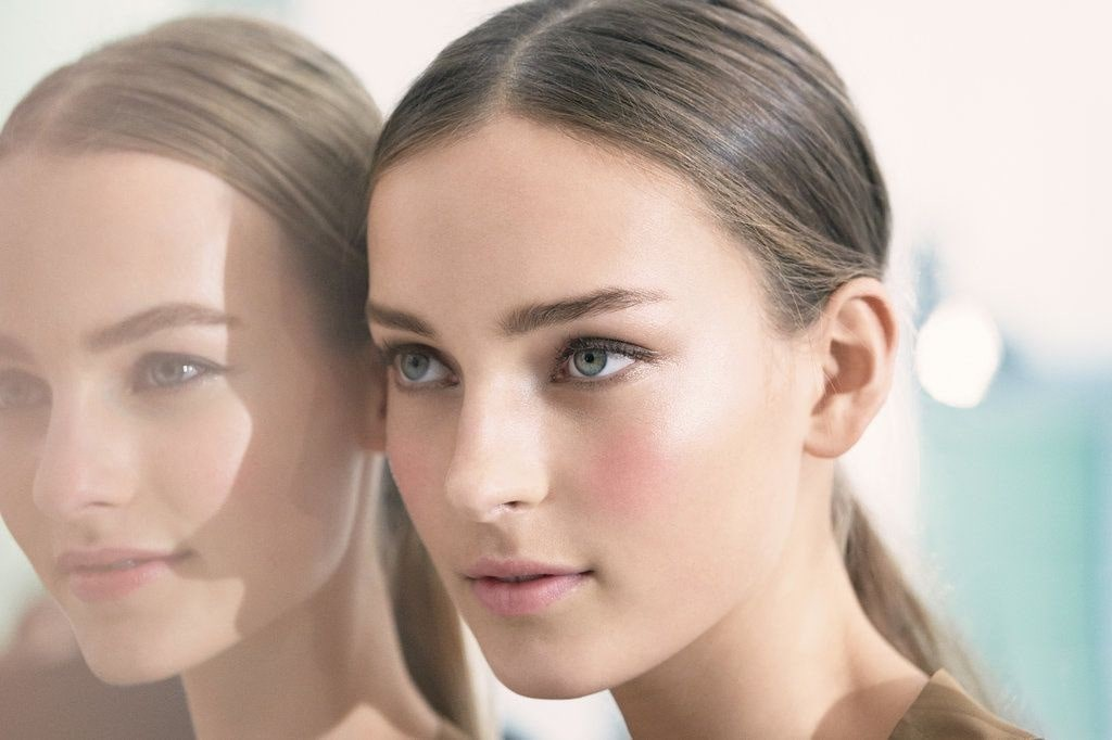 two female models posing with blush/rose cheeks.