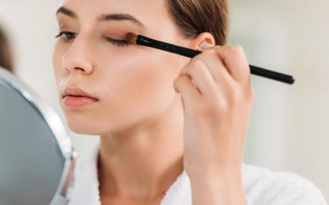 woman applying brown eyeshadow left-handed.