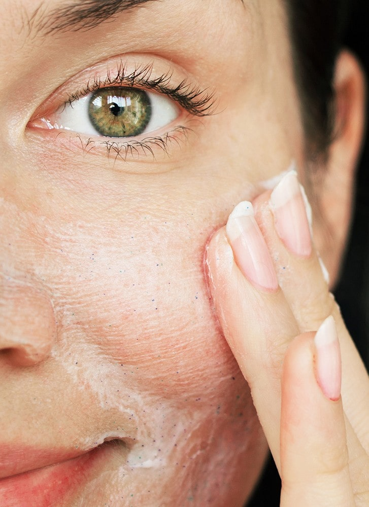 close up of a woman applying facial scrub to her cheek.