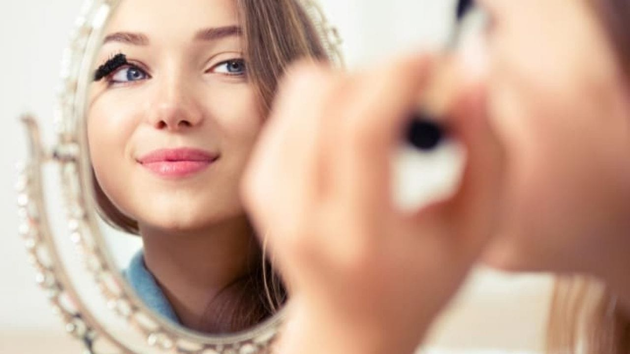 woman applying mascara using her left hand, whilst smiling into mirror.