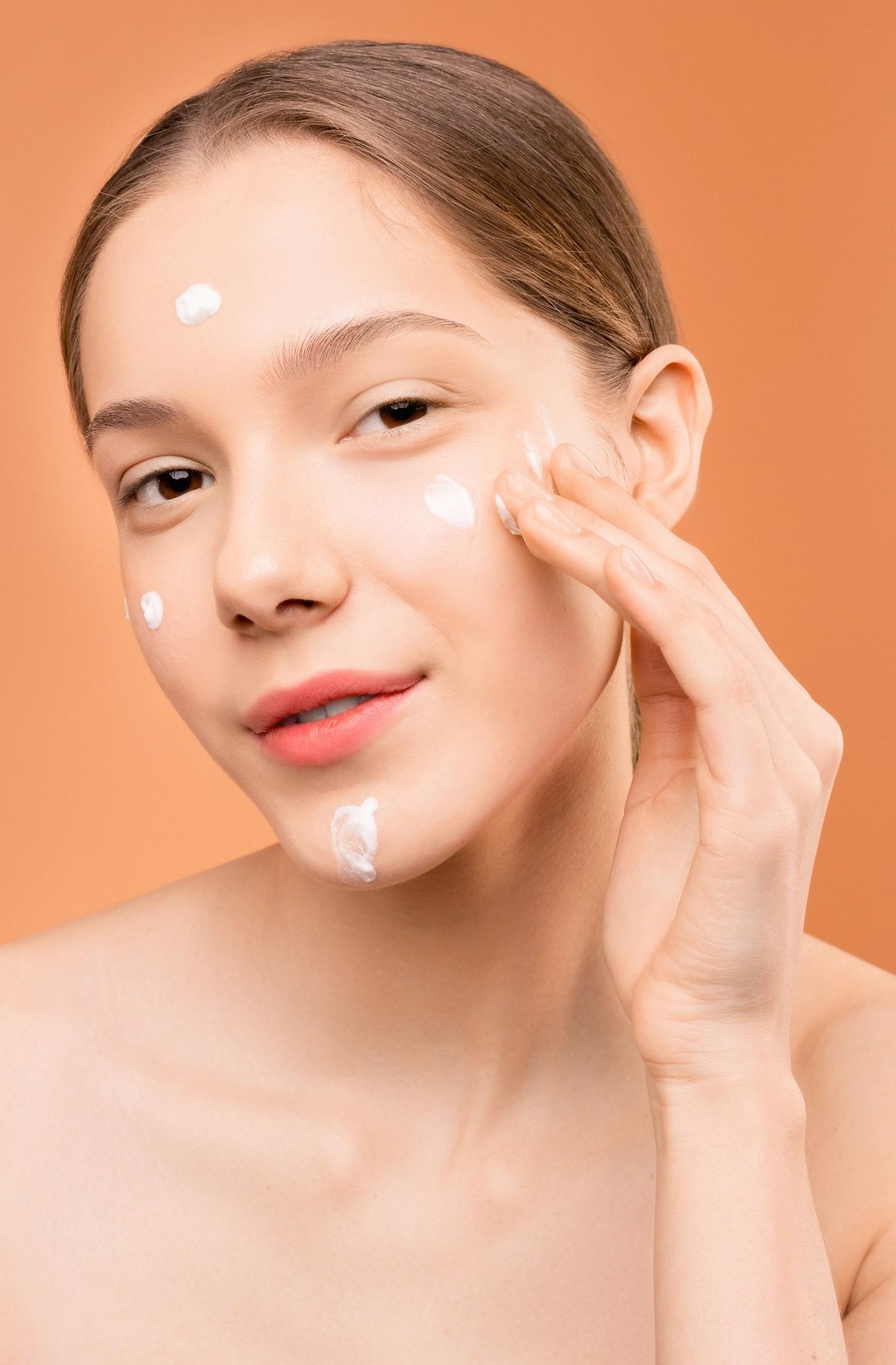 a woman applying moisturiser to her face