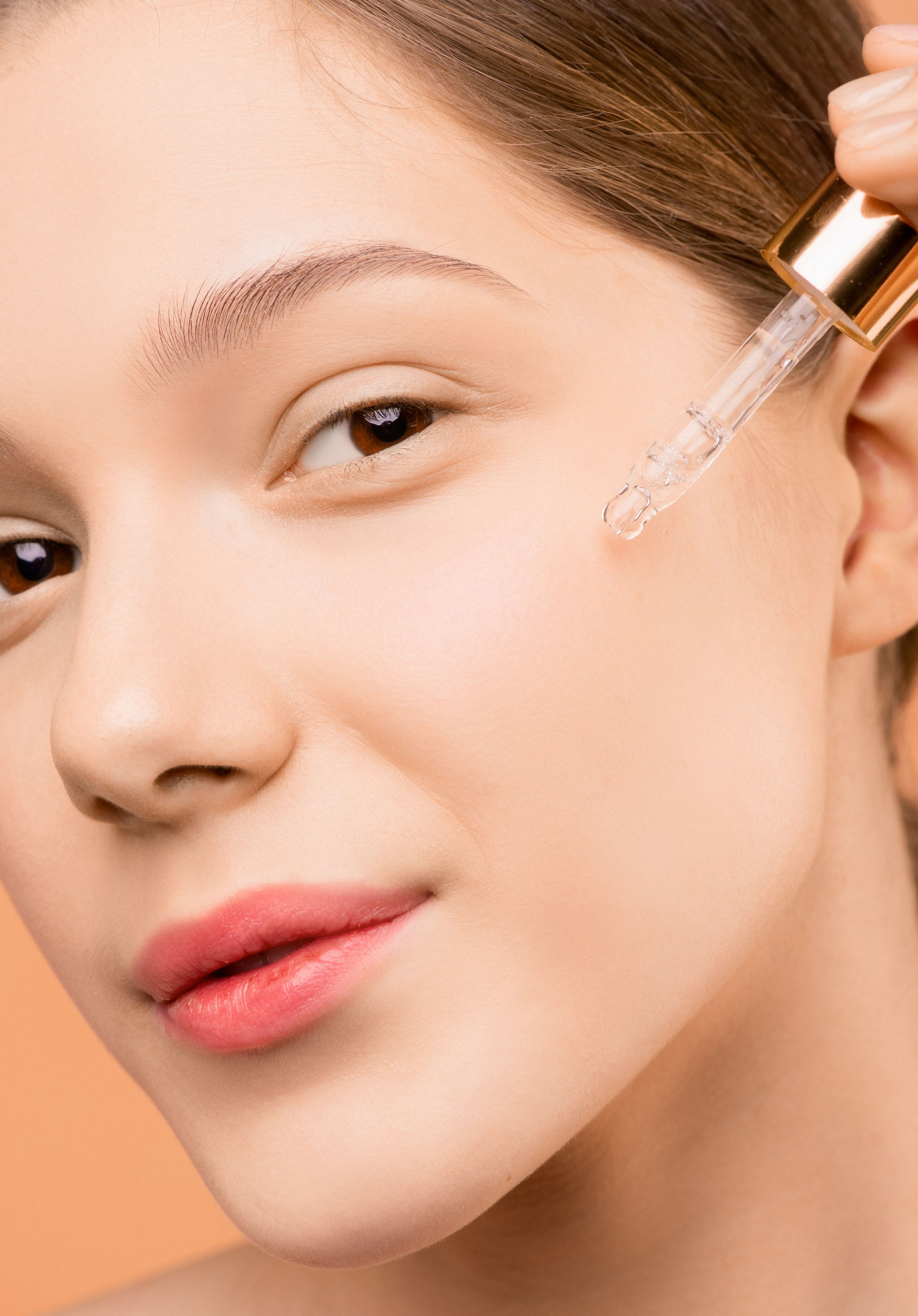 a woman applying facial oil to her skin/face