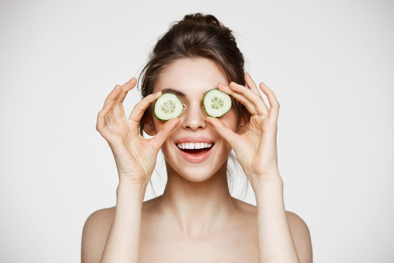 woman covering eyes with cucumber slices, laughing.