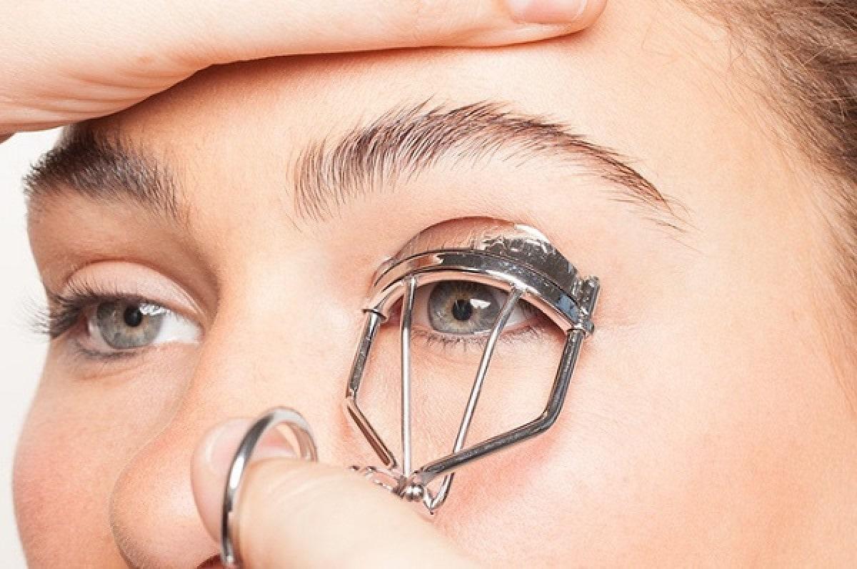 woman curling her eyelashes using eyelash curling tool.