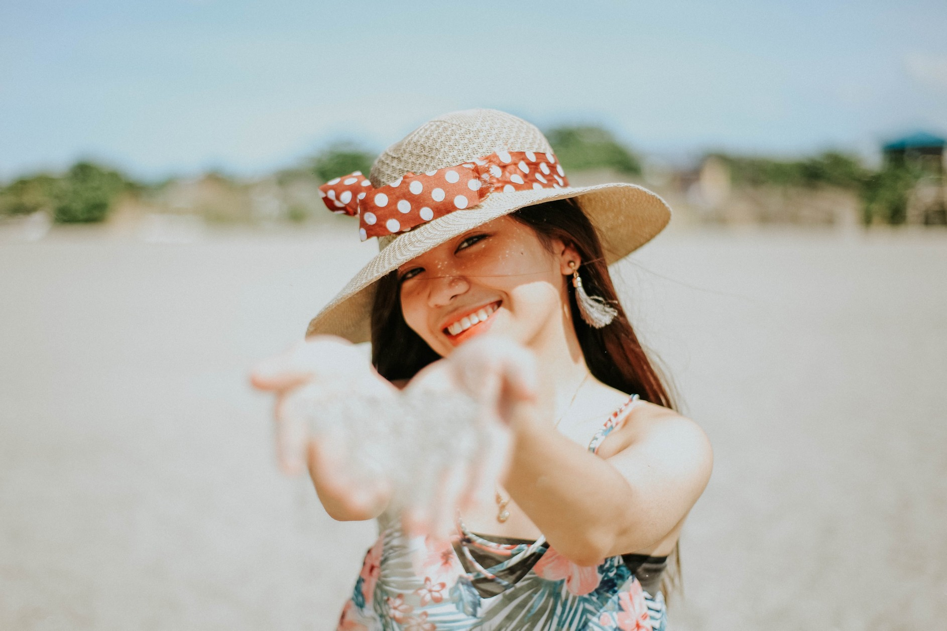 woman in a white and blue floral dress wearing a brown straw hat, pouring sand towards the camera whilst smiling.