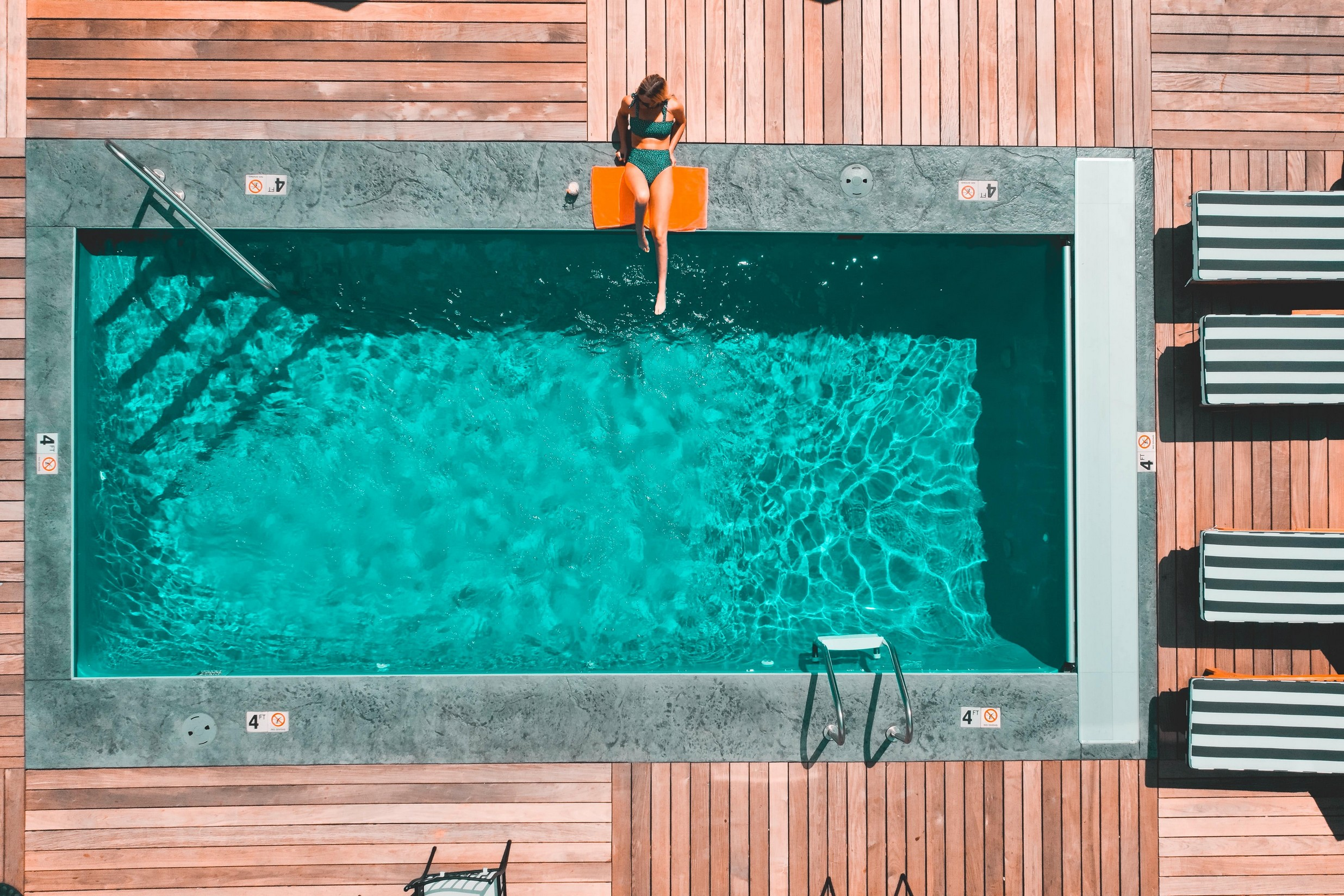 woman relaxing by outside pool.