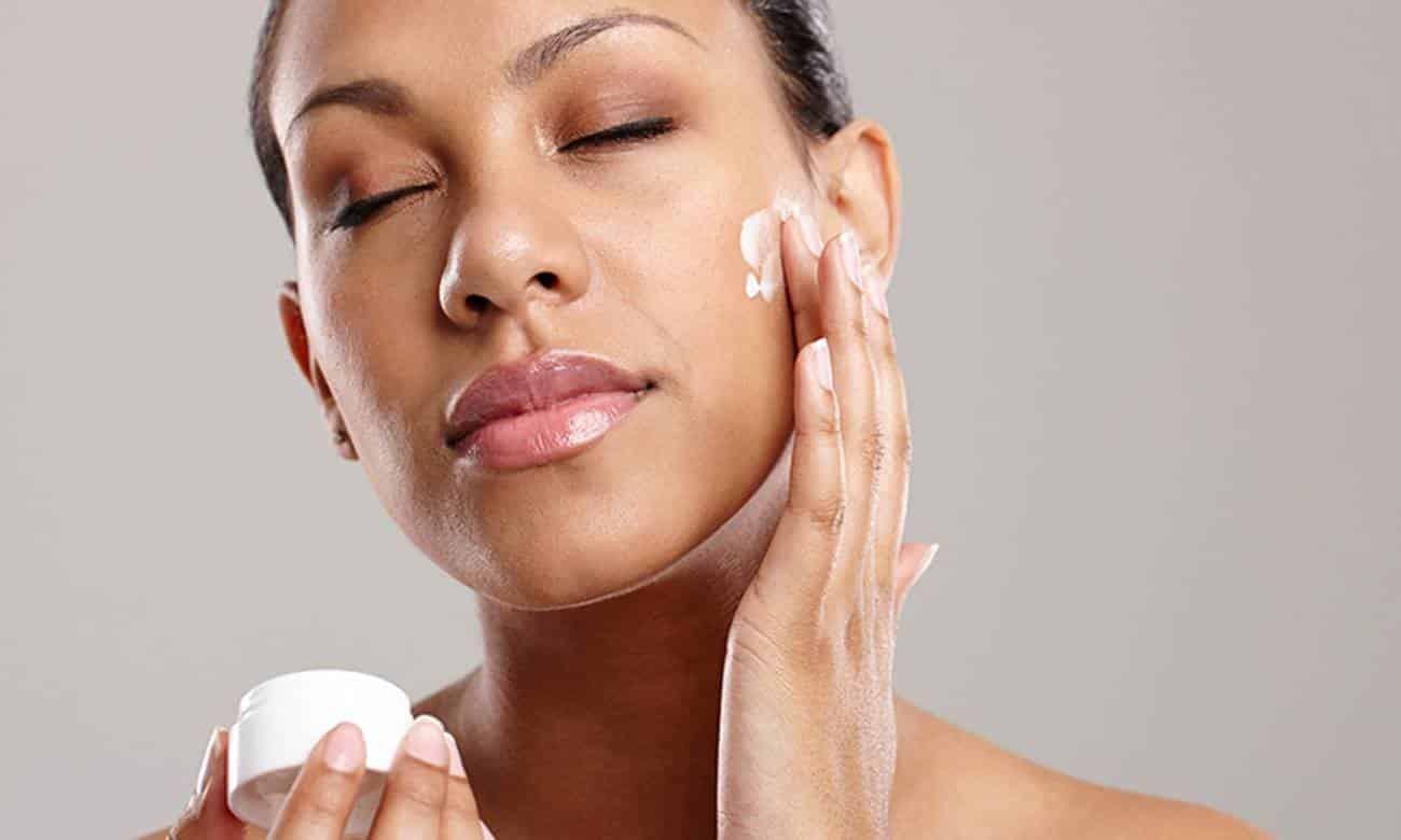 woman rubbing moisturiser into her skin - moisturising for acne-prone skin