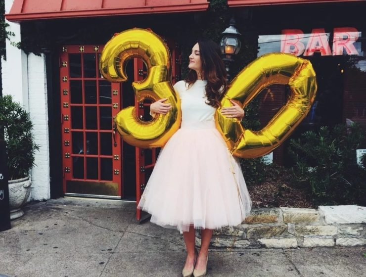 woman standing in a dress whilst holding two balloons, 3 and 0 / 30s.