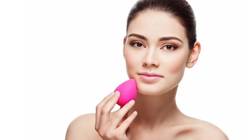 woman using a bright pink beauty blender on her face to apply makeup, with a white background.