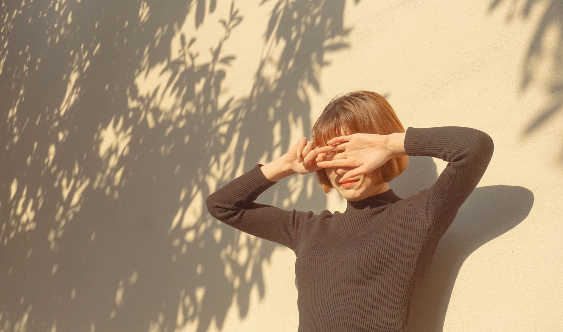 woman wearing black sweater shielding her face from the blinding sunshine.