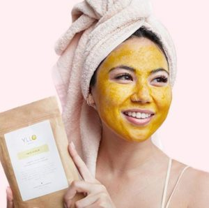 a woman with facial scrub on her face, smiling, whilst holding YLLO Facial Scrub packaging.