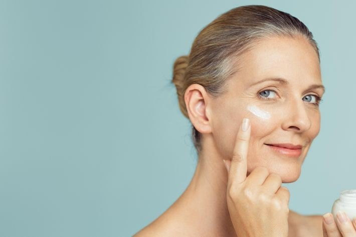 a woman applying anti-ageing cream and SPF to her face.