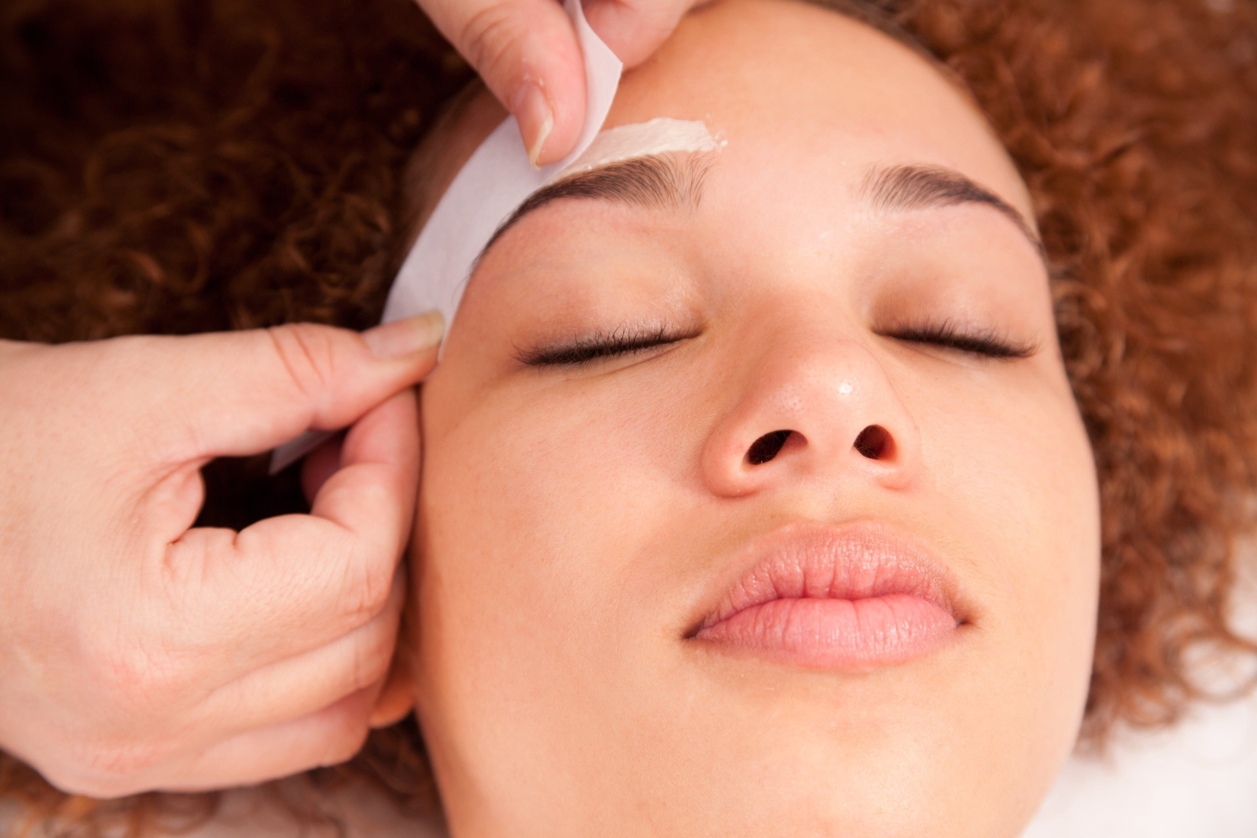 close up of a woman having her eyebrows waxed.