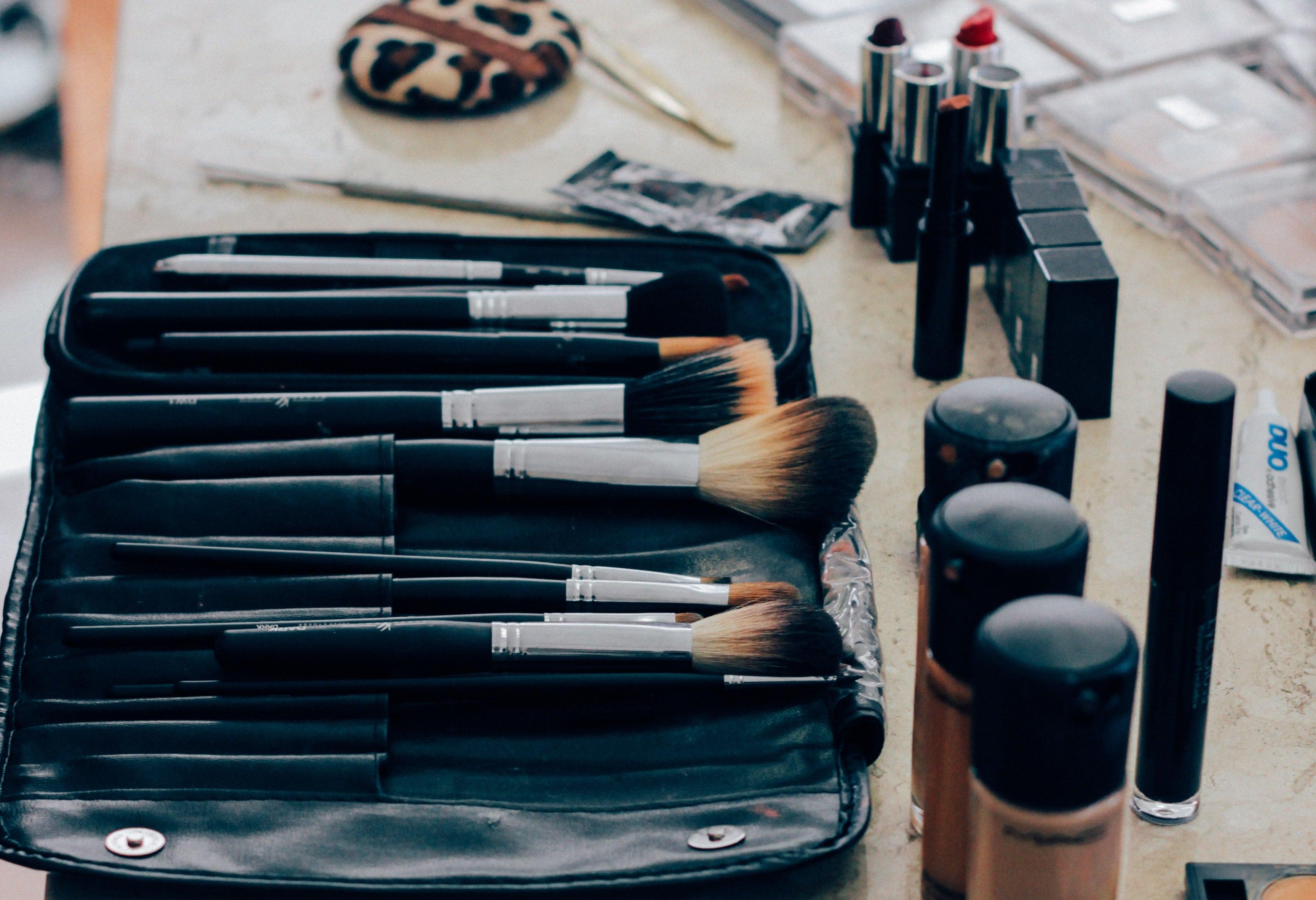 array of makeup brushes next to bottles of makeup.