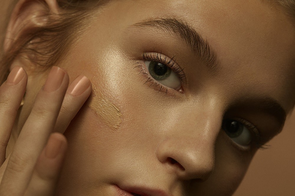 close up of a woman wearing tinted moisturiser on her cheek.