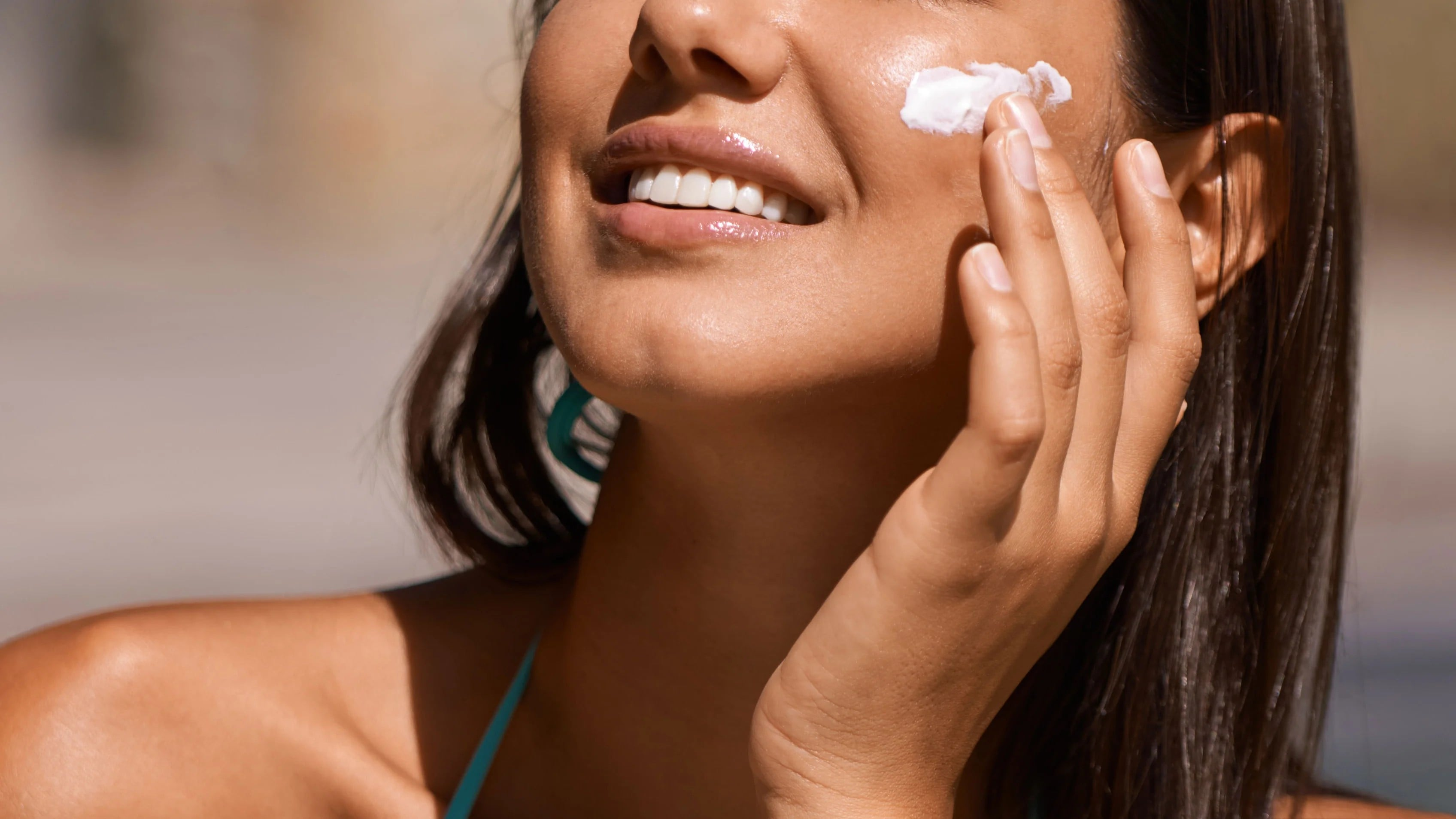 close up of a woman applying sunscreen over her makeup.