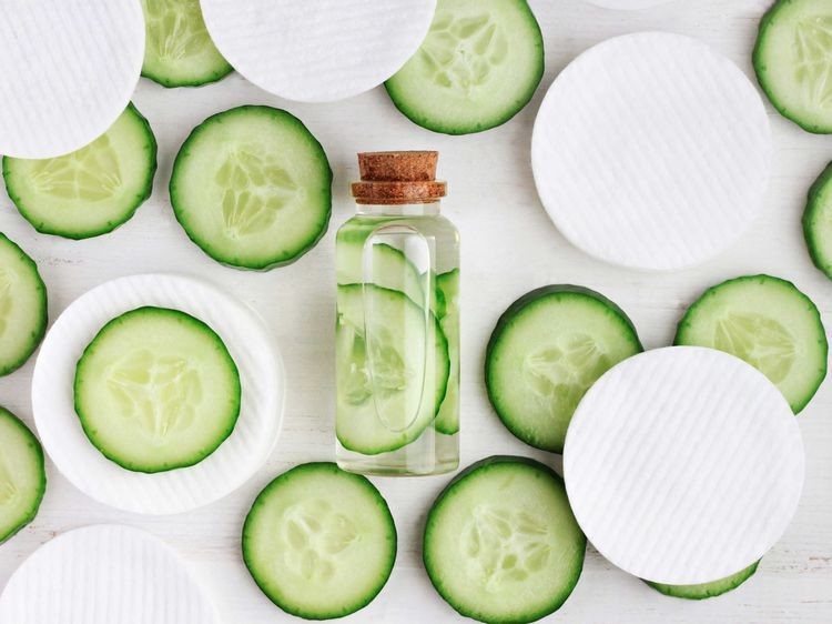 array of cucumber slices with a small glass bottle, containing cucumber slices and water, along with cotton pads.