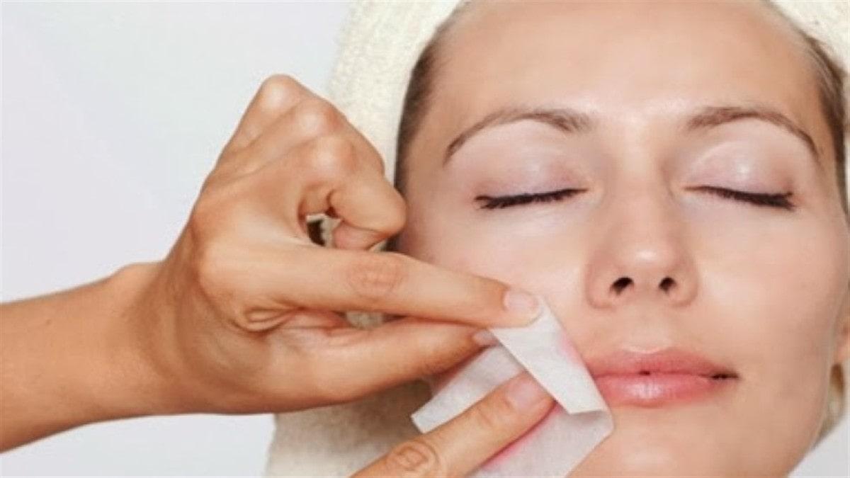 hand applying wax trip to around a woman's lips.