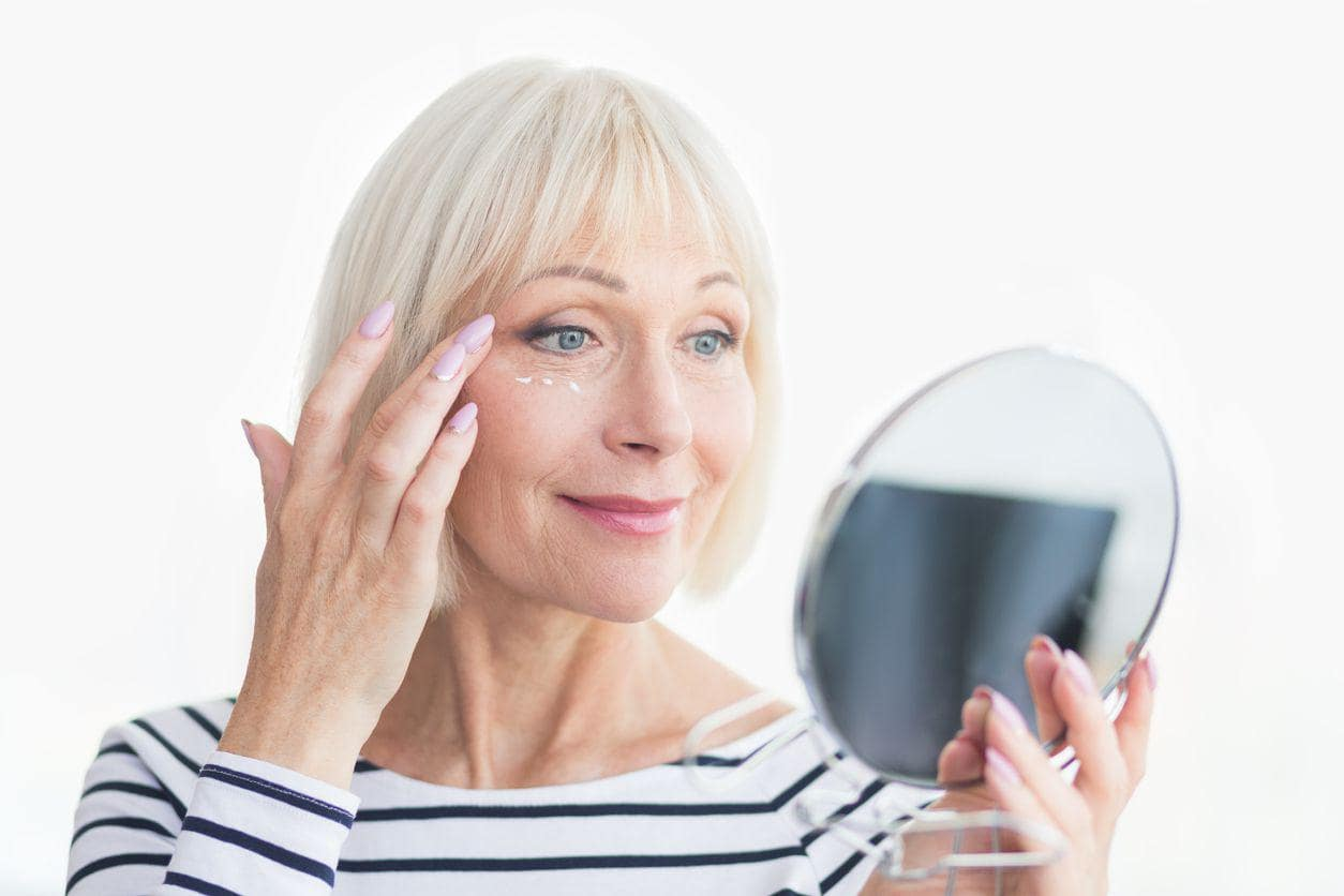 mature woman applying cream under her eyes whilst looking into the mirror.
