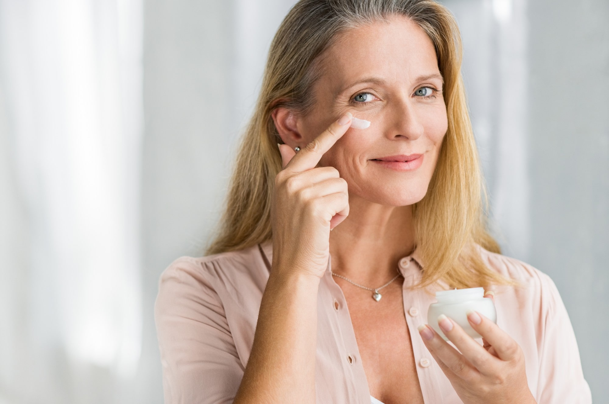 mature woman applying anti-ageing product to face.
