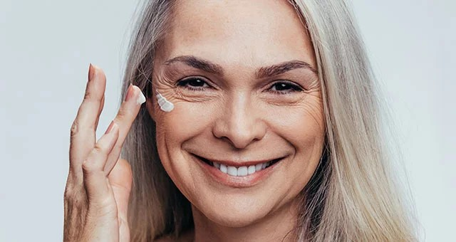 older woman applying anti-ageing cream to her face, smiling.