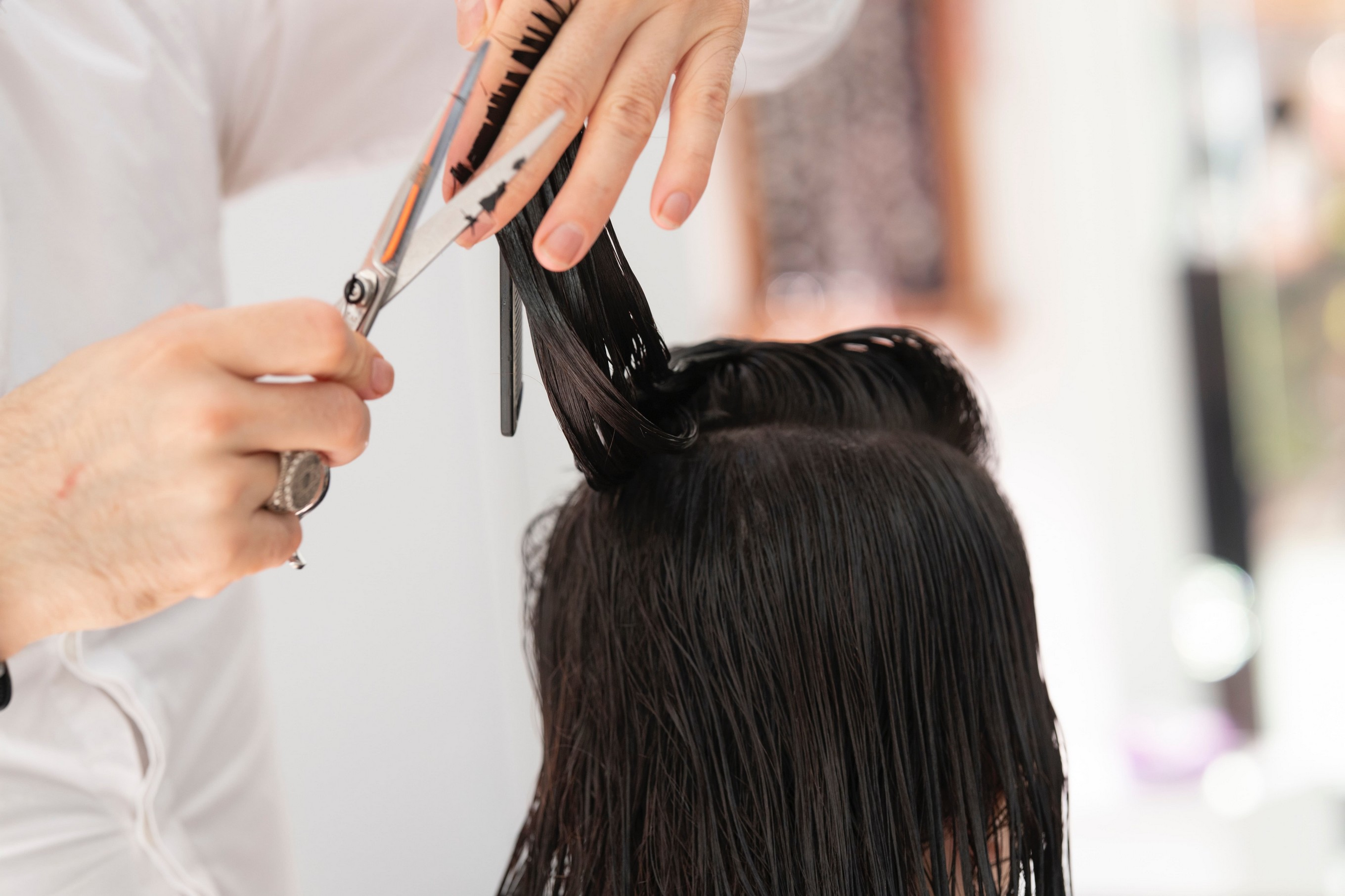 person cutting another individuals dark hair.