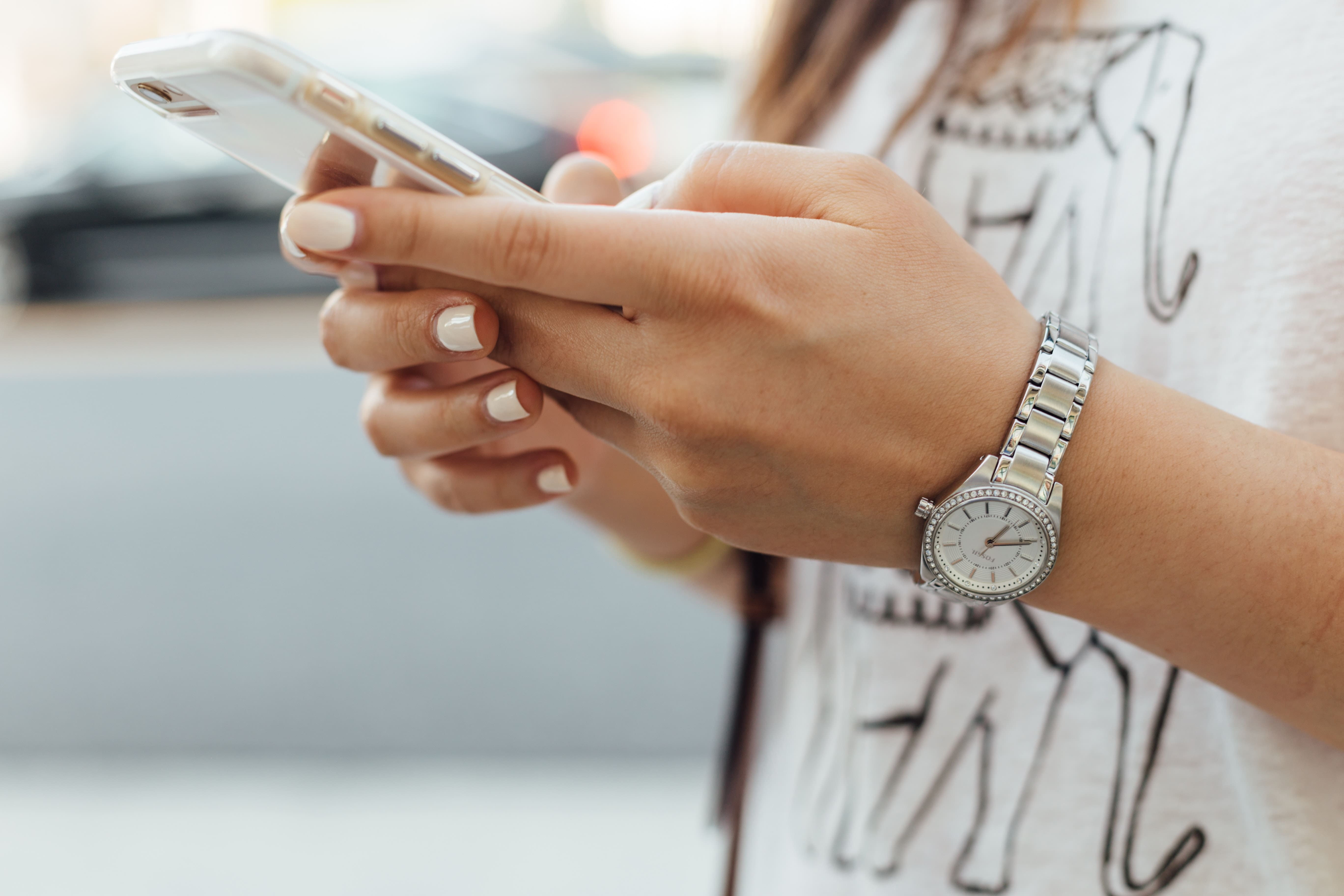 person holding mobile wearing a white top.
