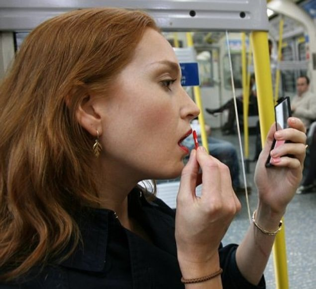 red haired woman applying makeup on tube during her commute.