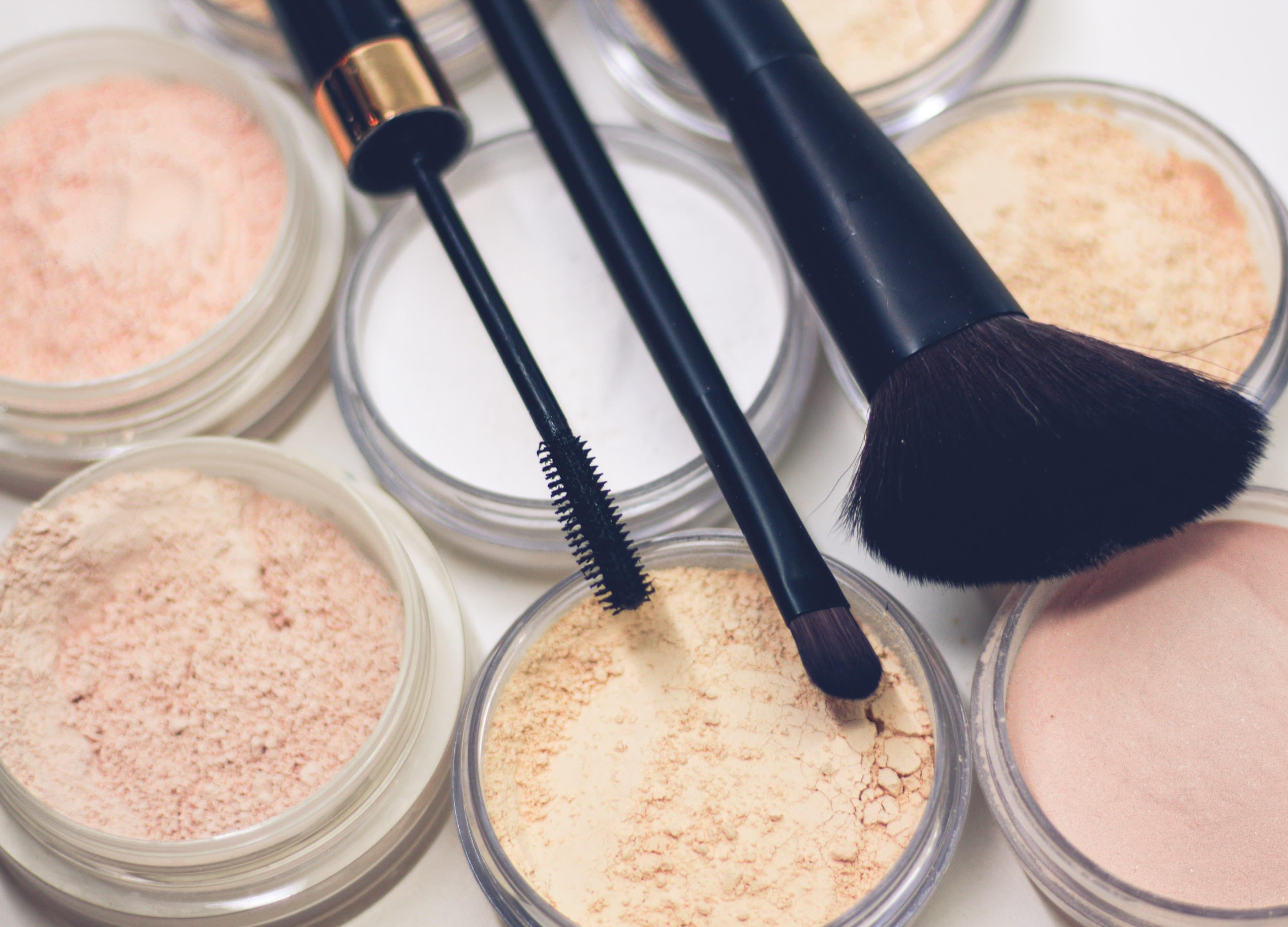various powder shades with makeup brushes.