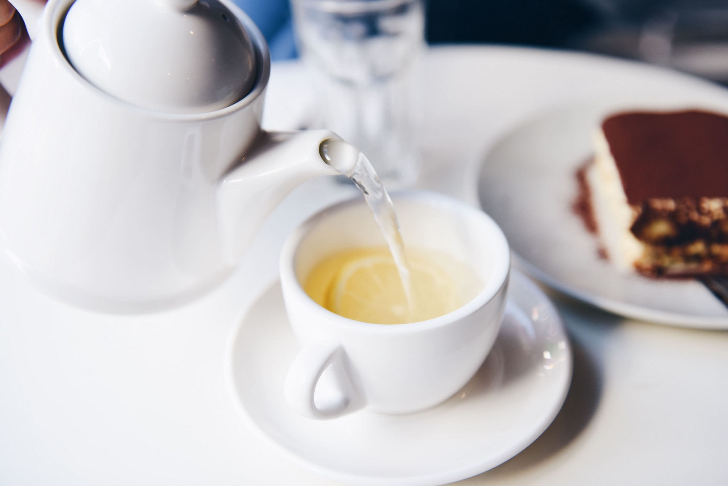 white cup and teapot, which is pouring clear liquid into the mug with a lemon slice.