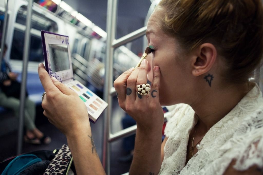 woman applying eyeshadow on the tube during her commute.