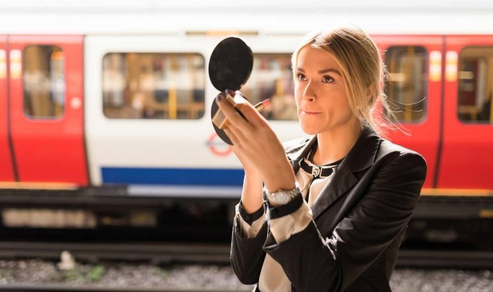 woman applying lipstick on the train platform.