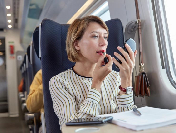 woman applying lipstick whilst on a train on her commute.