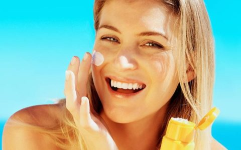 woman applying sun protection to her face.
