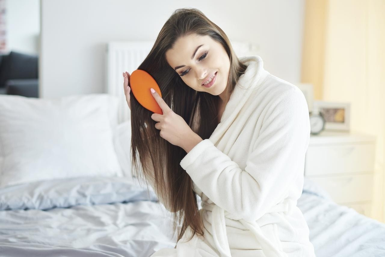 Hair Myths: Woman brushing her hair whilst sitting on her bed.