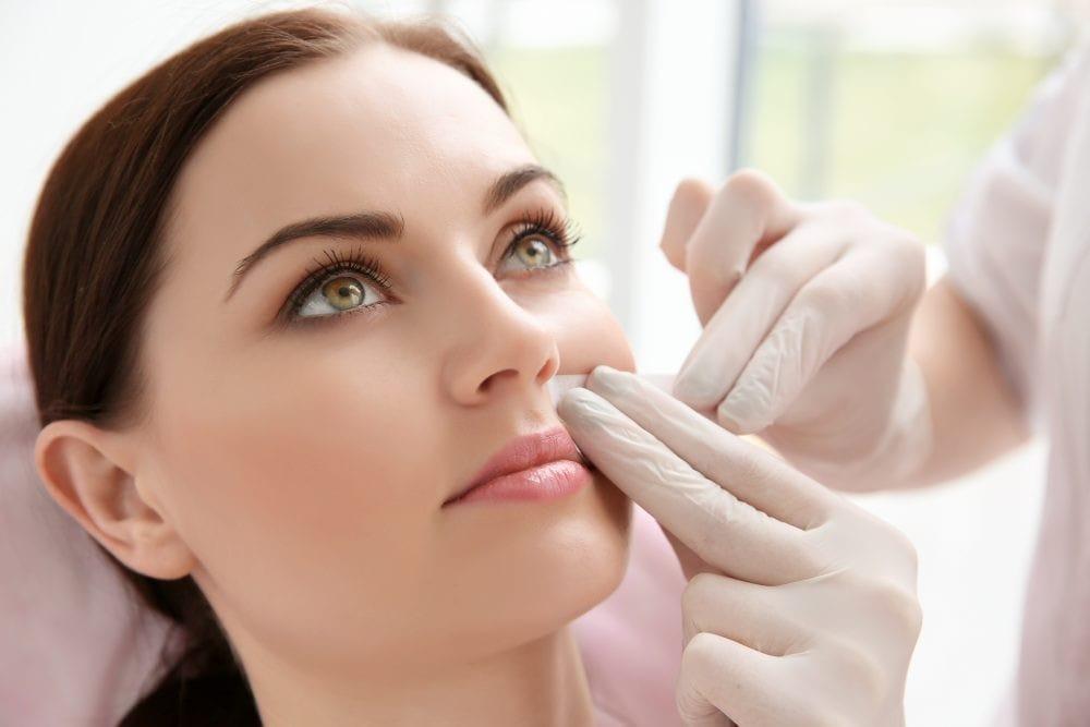 woman having her upper lip waxed.