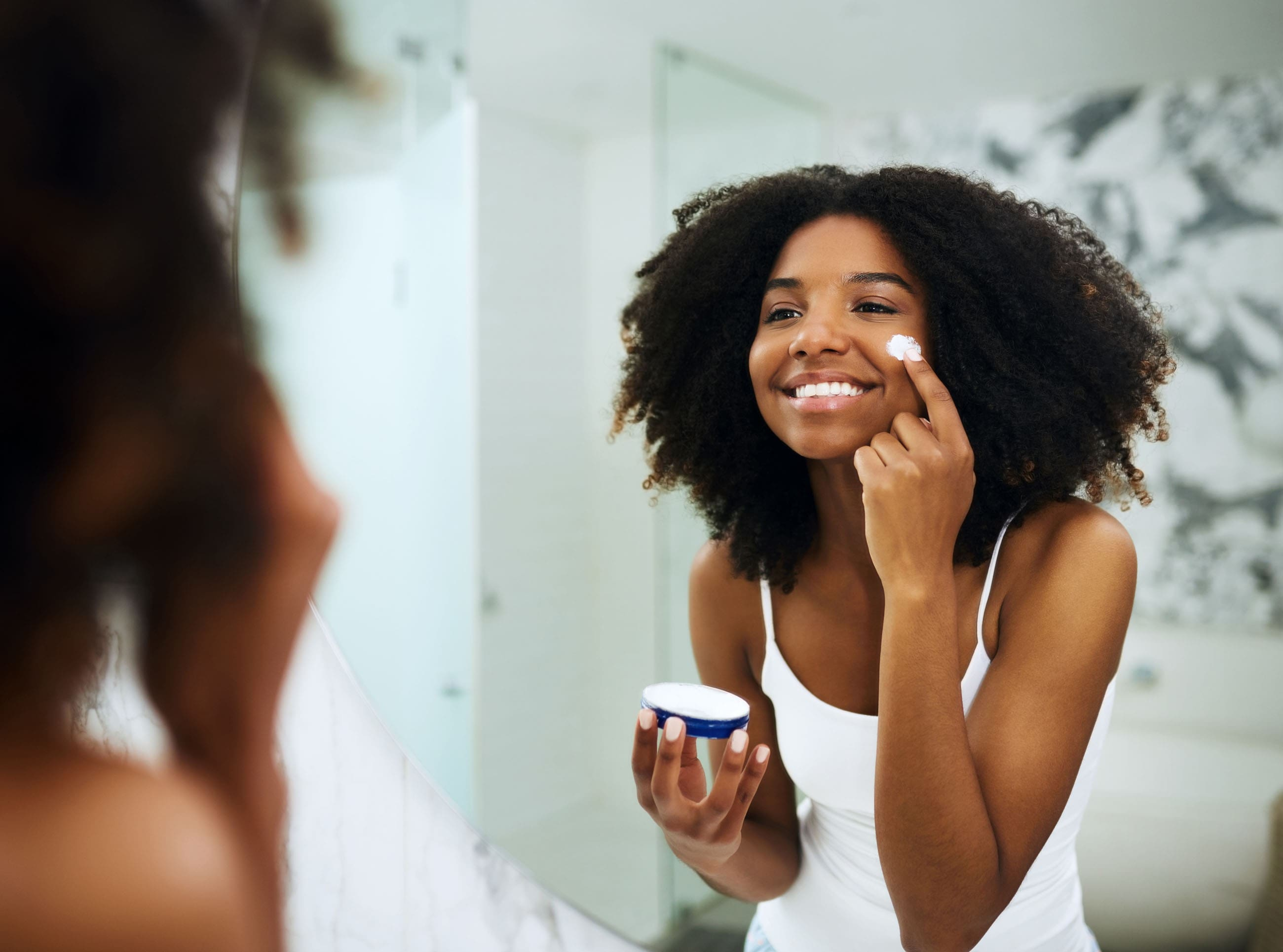 woman standing in front of a mirror, holding a small pot of cream and applying sun protection.