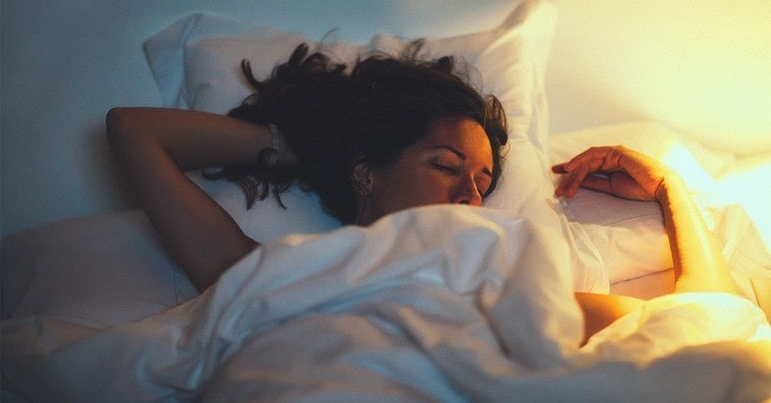woman sleeping in bed with light on next to her.