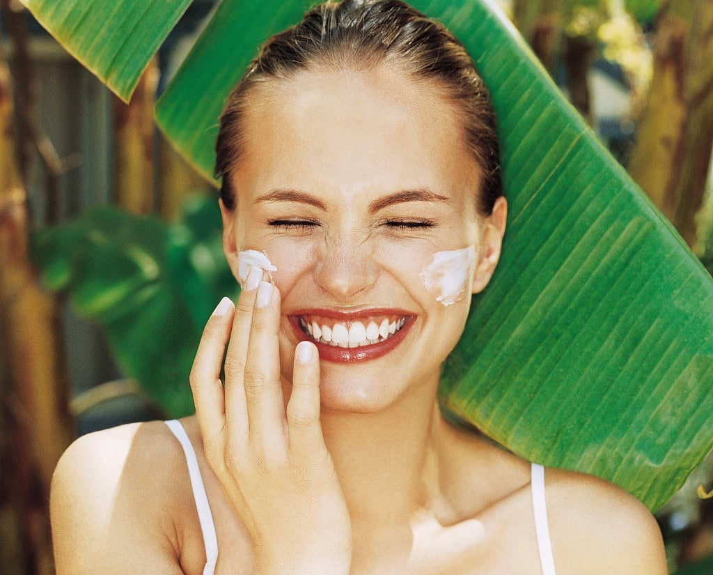 a woman laughing, whilst rubbing sun protection into her cheeks.