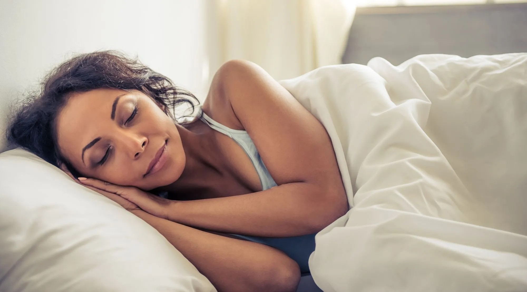 woman sleeping under a white duvet.