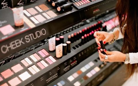 woman standing, trying products, at a makeup testing counter.
