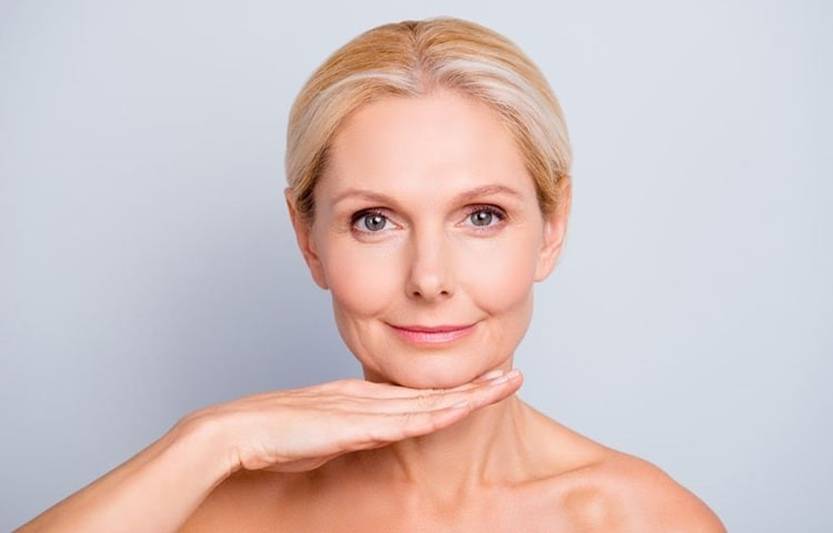 woman, after applying anti-ageing products, touching her chin with the back of her hand.
