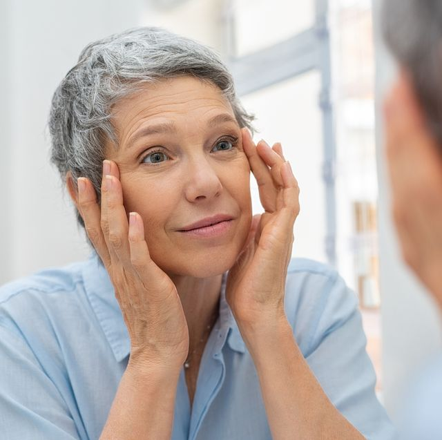 Anti-Ageing: woman touching her face, whilst looking in the mirror, with a thoughtful expression
