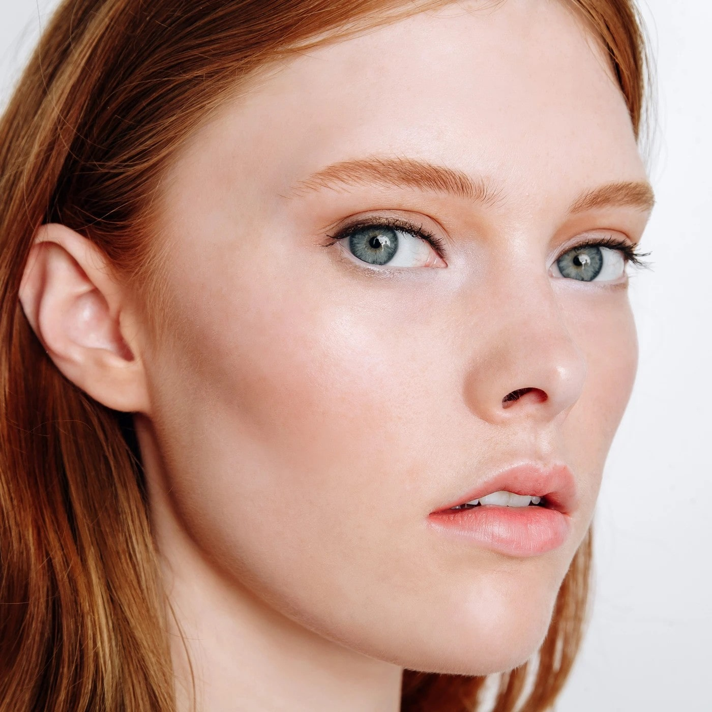 woman with auburn hair wearing tinted moisturiser.