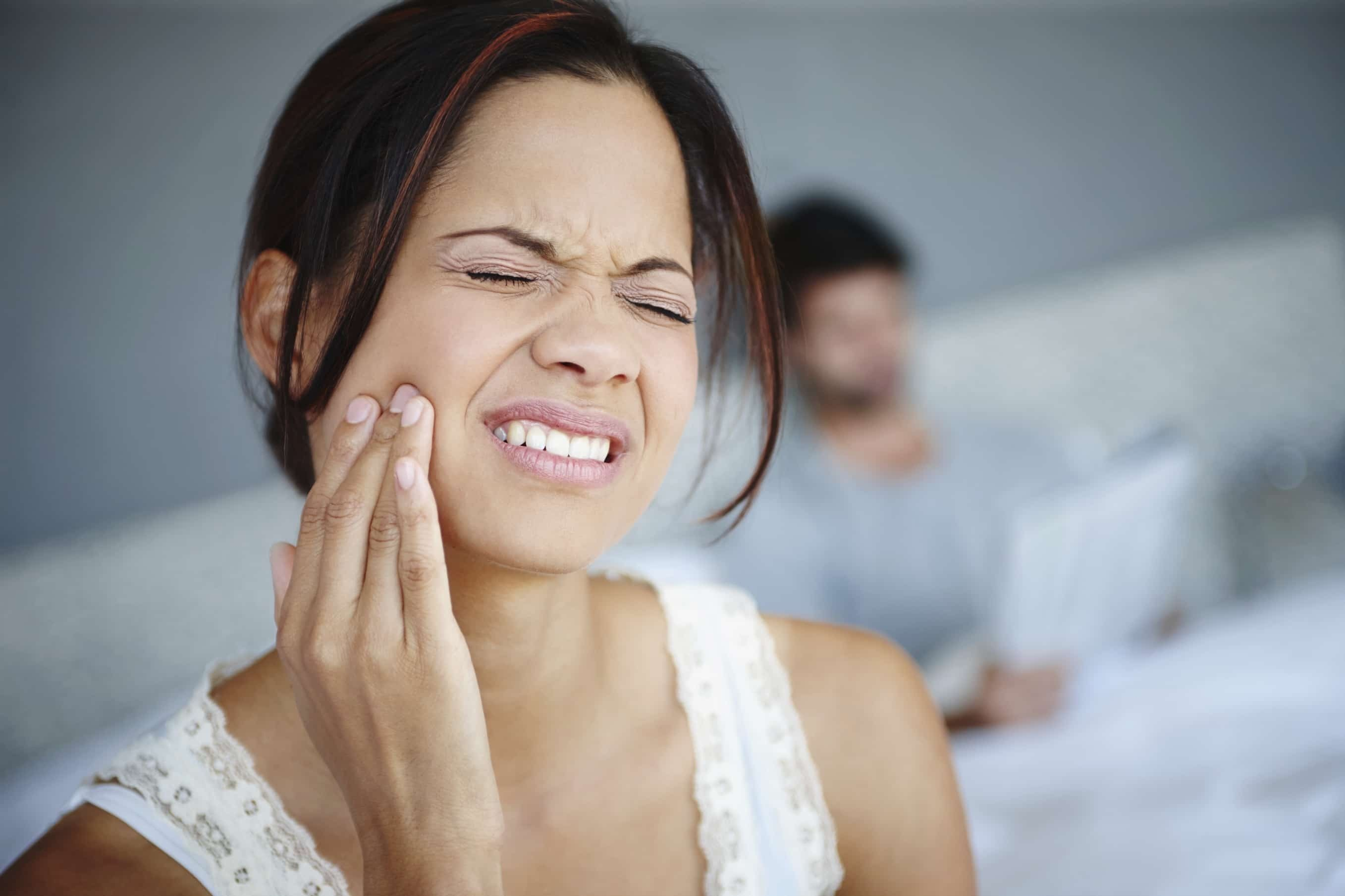 woman with pained expression touching her face.