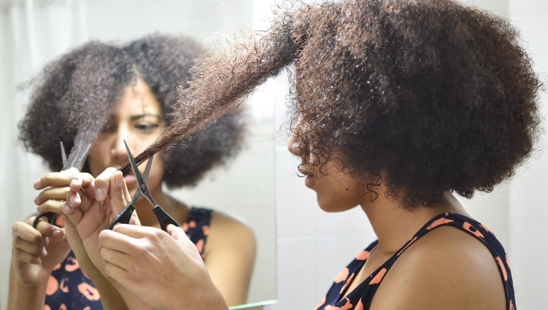 a woman with curly hair cutting the ends of her hair in front of the mirror.